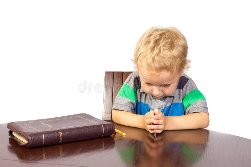 Blond weinig jongen die aan God na het lezen van de bijbel bidden stock afbeelding