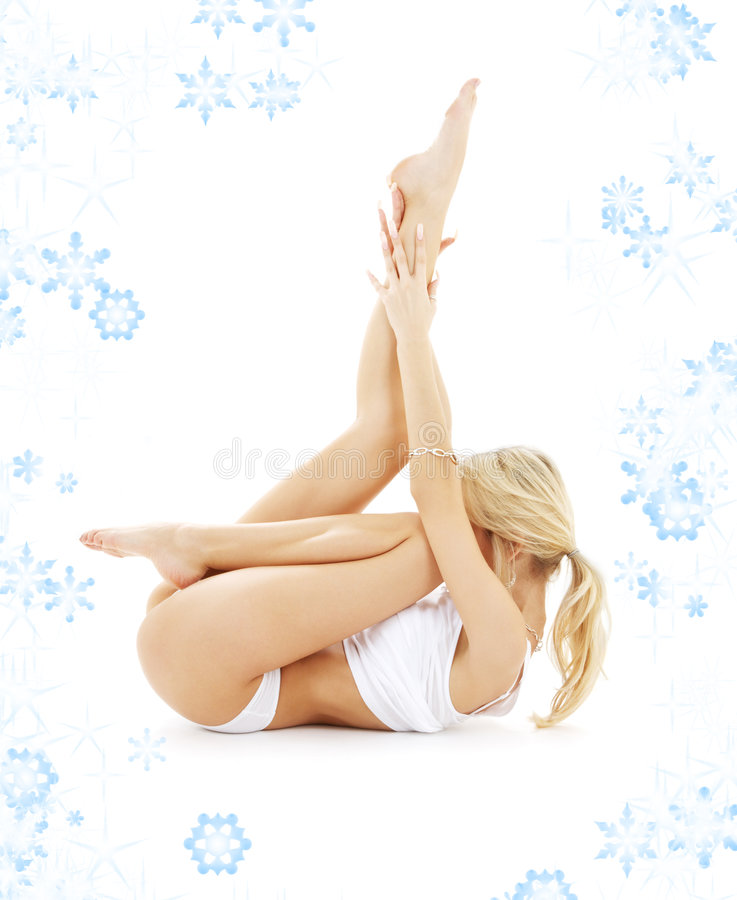 Blond in white underwear practicing yoga with snow stock images