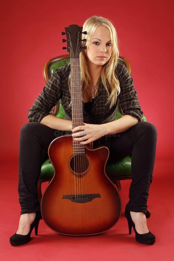 Blond wijfje met akoestische gitaar stock fotografie