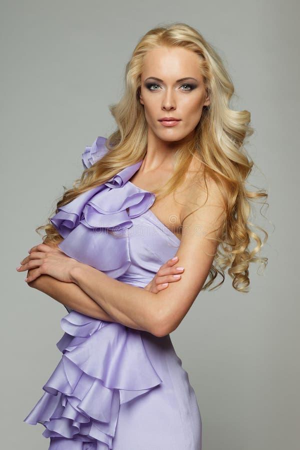 Blond wijfje in purpere kleding stock afbeeldingen