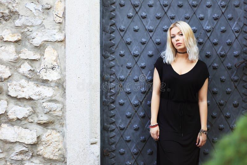 Blond woman. Beauitul blond woman posing near castle wall royalty free stock photos