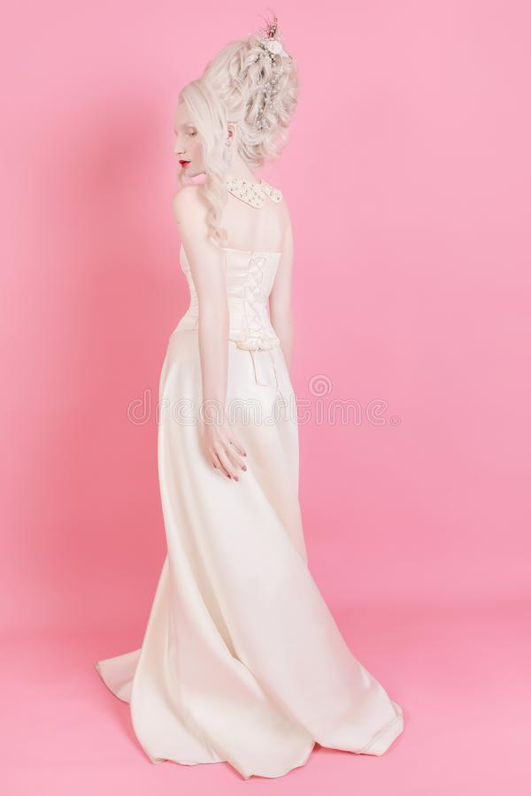 Woman with beautiful luxurious rococo hair style in white dress. A blond woman with a beautiful luxurious rococo hair style in a white dress on a pink background stock photography