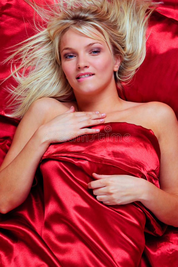 Blond woman biting her lip in bed royalty free stock photo