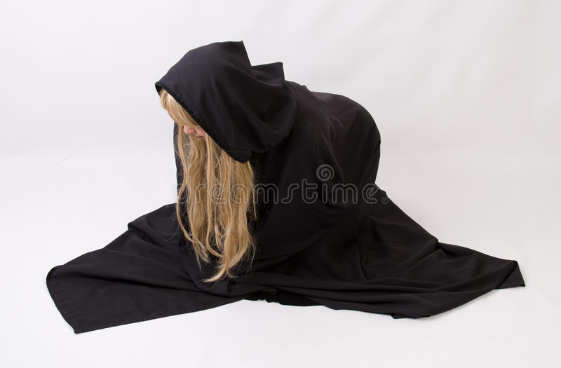 Blond woman in black hooded cloak. Bent over in grief or pain stock photos