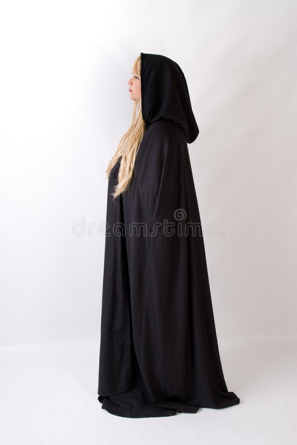 Blond woman in black hooded cloak side view. Woman with long blonde hair is turned to the side in a full length black hooded cloak with medieval look stock photography