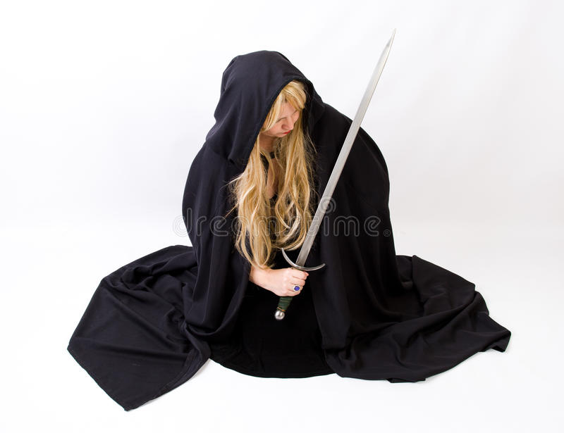 Blond woman in black hooded cloak with sword. Woman with long blonde hair and full length black cloak brandishes a long silver sword and purple magical ring royalty free stock image
