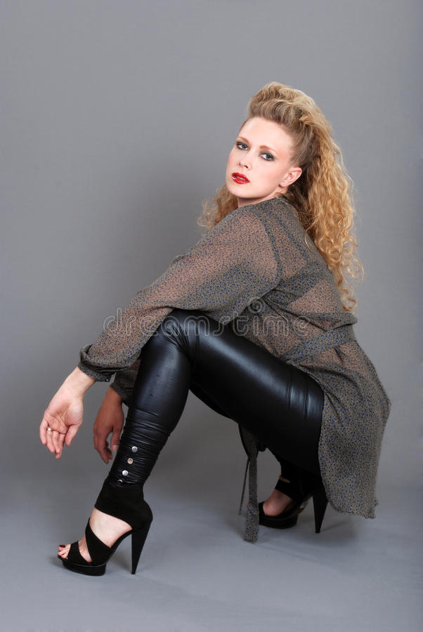 Blond woman with black leather pants squatting. Portrait of blond woman with black leather pants squatting on gray background stock image