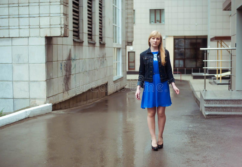 Blond woman in blue dress and denim jacket walking down the city street against background of urban architecture royalty free stock image
