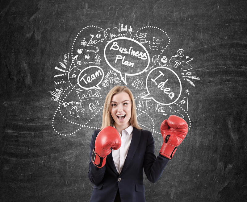 Blond woman in boxing gloves and business idea sketch. Cheerful businesswoman in boxing gloves is standing near chalkboard with business plan sketch on it stock image