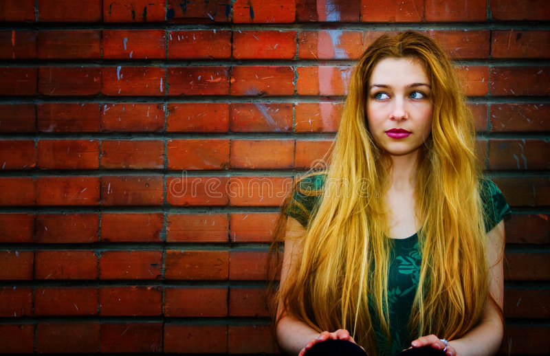 Blond woman and brick wall