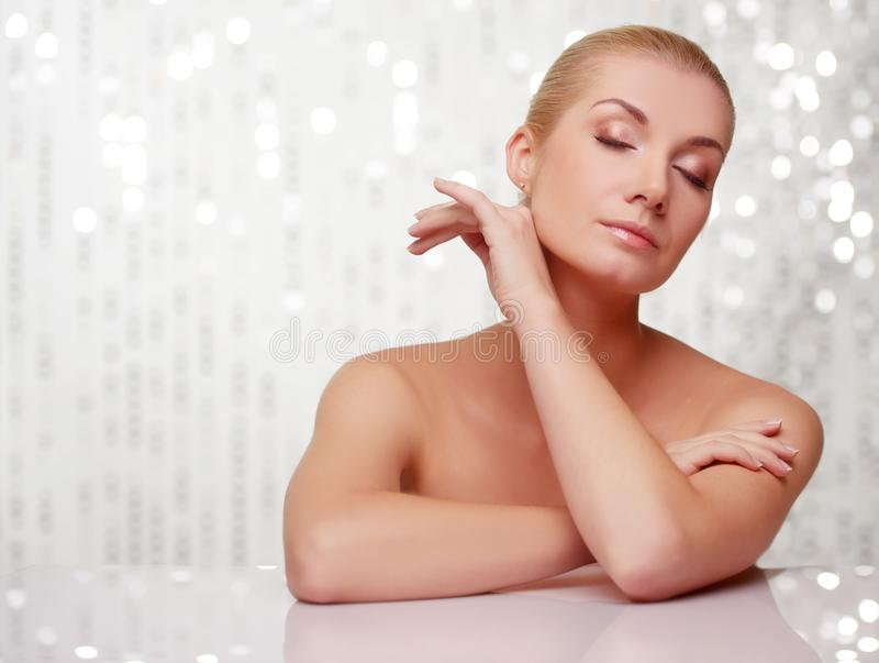 Download Blond Woman With Closed Eyes Behind Table Stock Photo - Image: 24452996