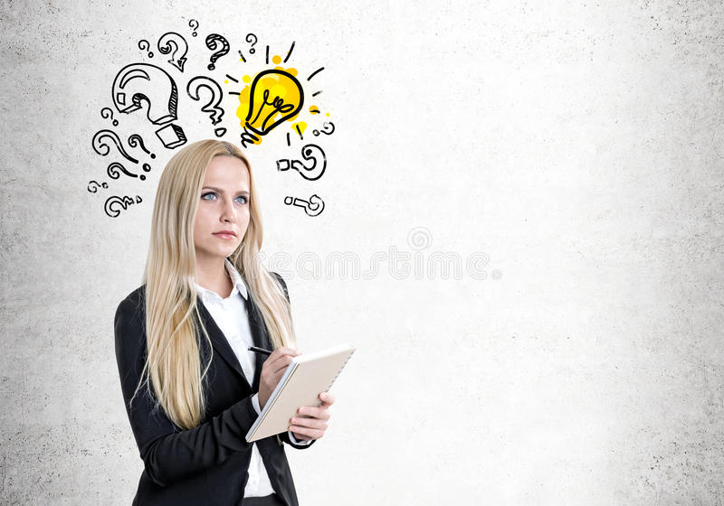 Blond woman with a copybook, questions, bulb stock photography