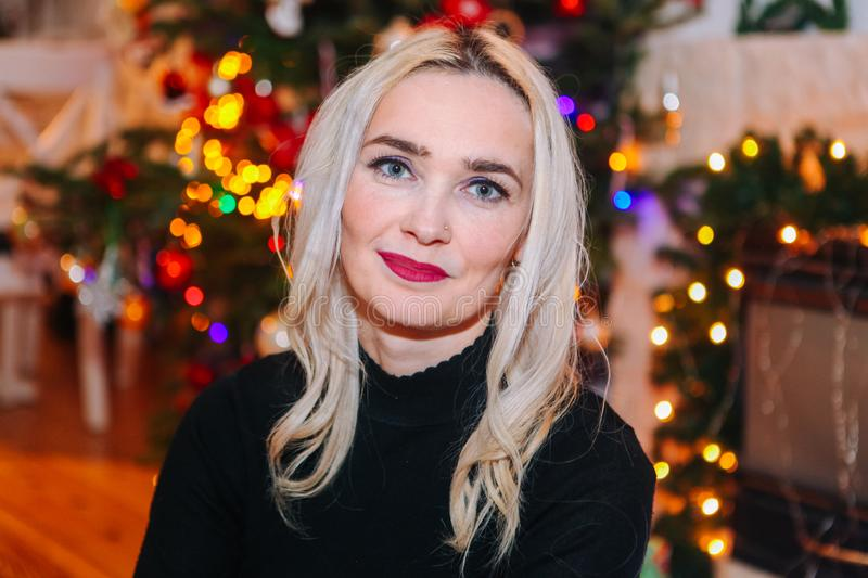 Blond woman with curly hair sit under christmas tree stock photos