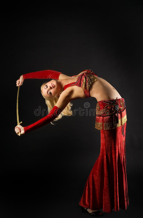 Blond woman dance with saber. In dark stock photo