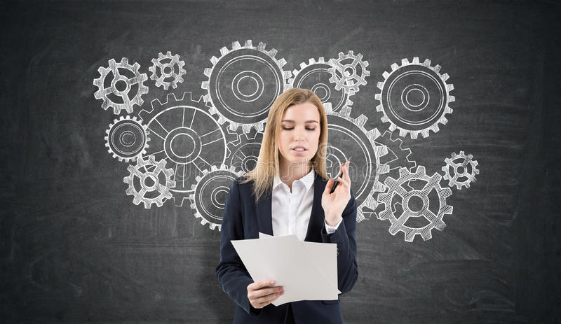 Blond woman with documents and cogs and gears sketches on a chalkboard royalty free stock images