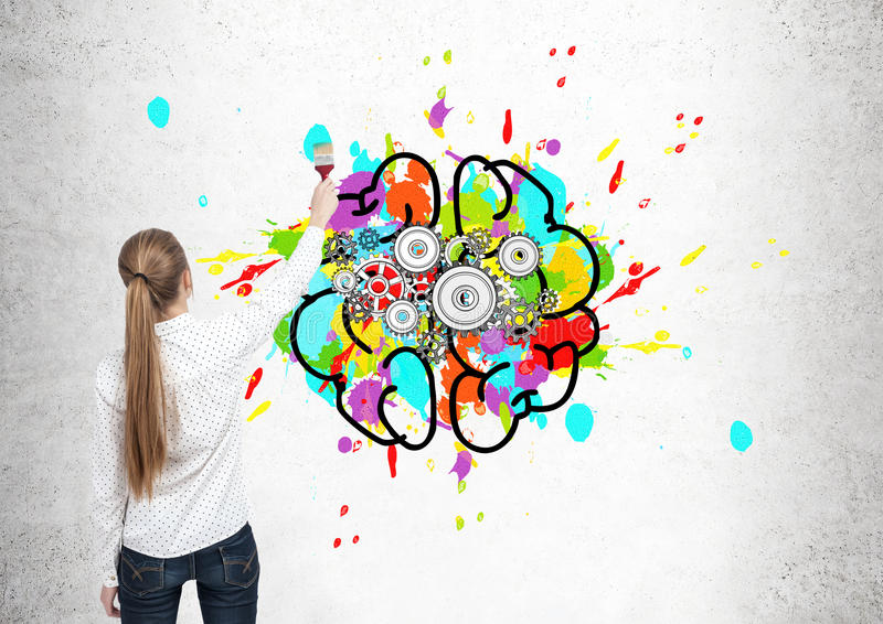 Blond woman drawing brain with cogs stock image