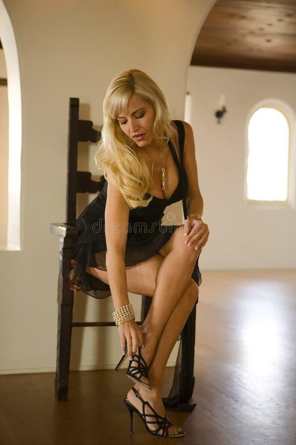 Blond Woman Fixing her Shoe. Beautiful Blond Woman fixing her Shoe looking down stock images