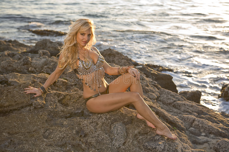 Blond Woman in Flashy Outfit on Rocks. Blond Woman in outfit sitting on rocks at the beach royalty free stock image