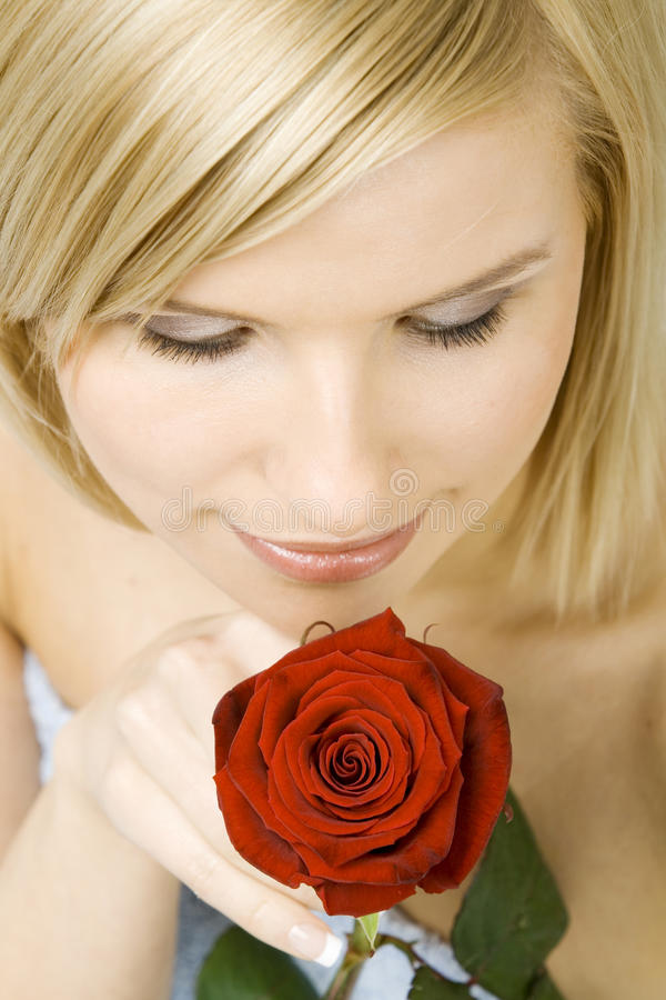 Blond woman with fresh rose stock photography