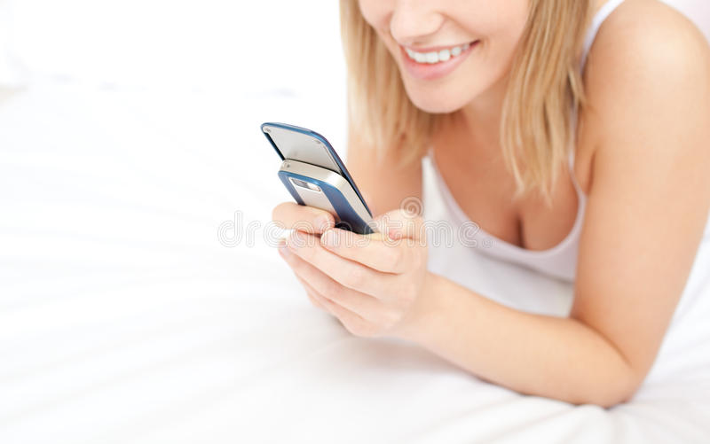 Download Blond Woman Giving A Text Message Lying Down On Be Stock Images - Image: 13889204