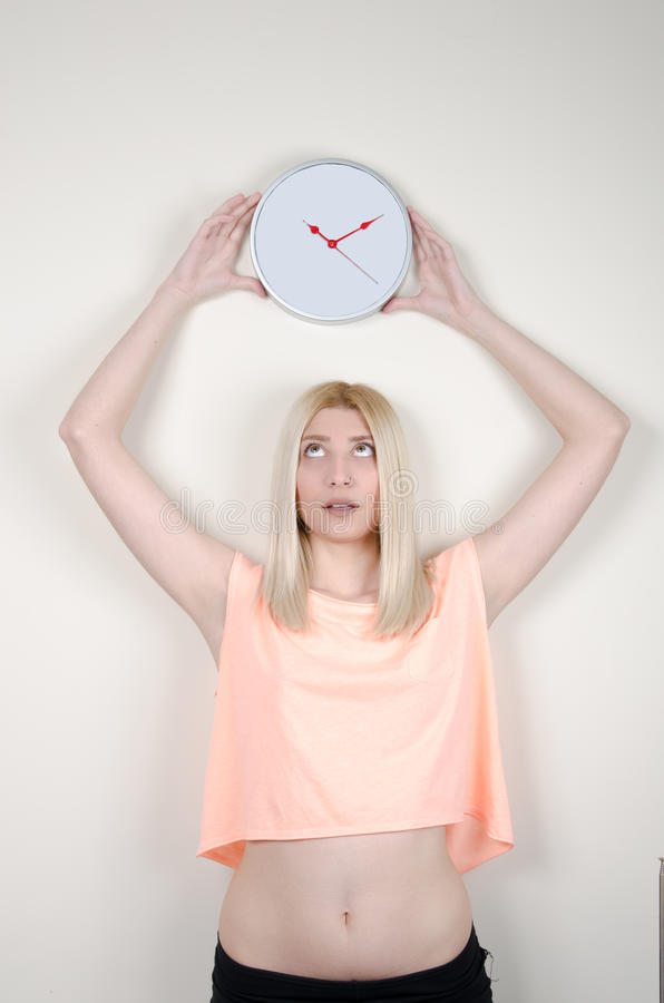 Blond woman with green eyes leaning on white wall, holding a wall clock royalty free stock photos