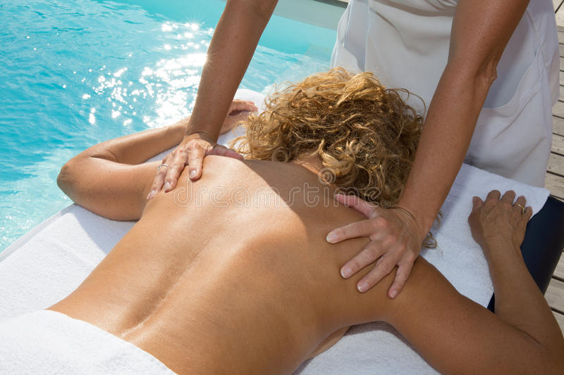 Blond woman having a back massage in a spa center royalty free stock photos