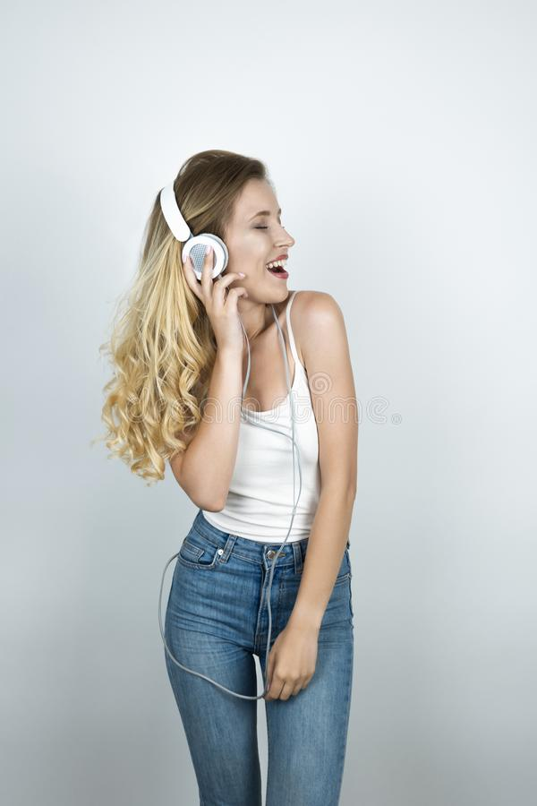 Blond woman holding her headphones with one hand listening to music smiling white  background royalty free stock photos