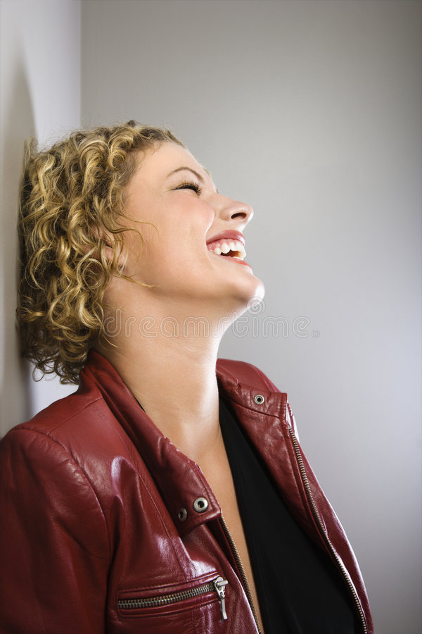 Blond woman laughing. Profile of Caucasian young adult woman in red jacket leaning back against wall laughing stock images