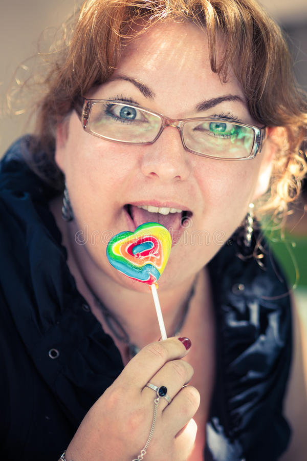 Blond woman with a lollypop stock images