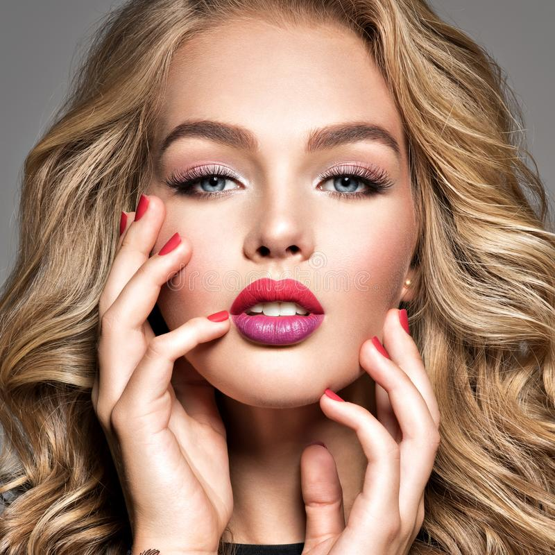 Blond woman with long curly beautiful hair. Makeup. Fashion make-up stock photos