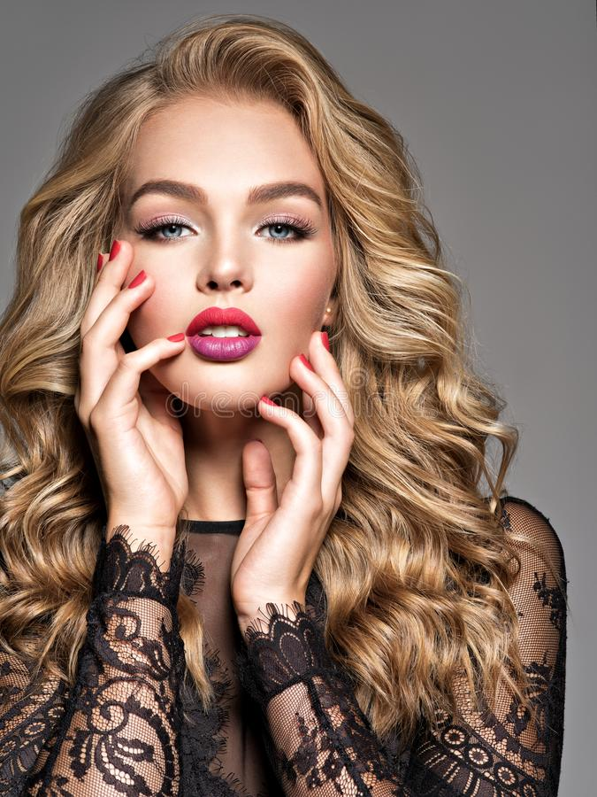 Blond woman with long curly beautiful hair. Makeup. Fashion make-up stock image