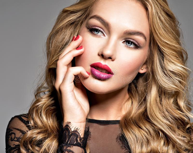 Gorgeous woman with long curly beautiful hair. Makeup. Bright colored lips stock photo
