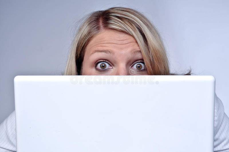 Blond Woman Looking Behind Laptop Stock Image