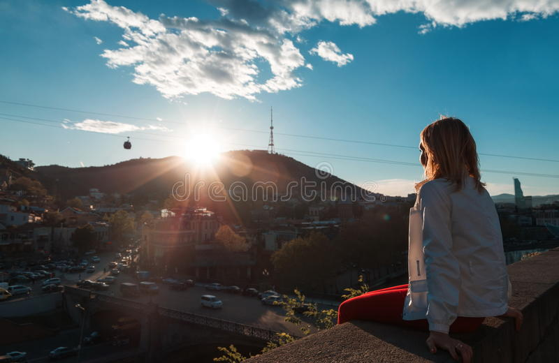 Blond woman looking at the city. At sunset stock photos