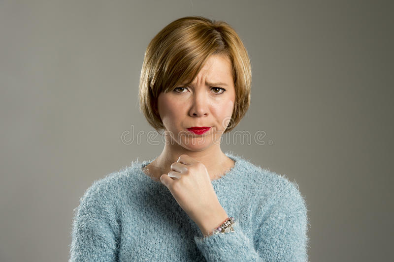 Blond woman looking suspicious and grumpy in discontent and tension face expression royalty free stock images