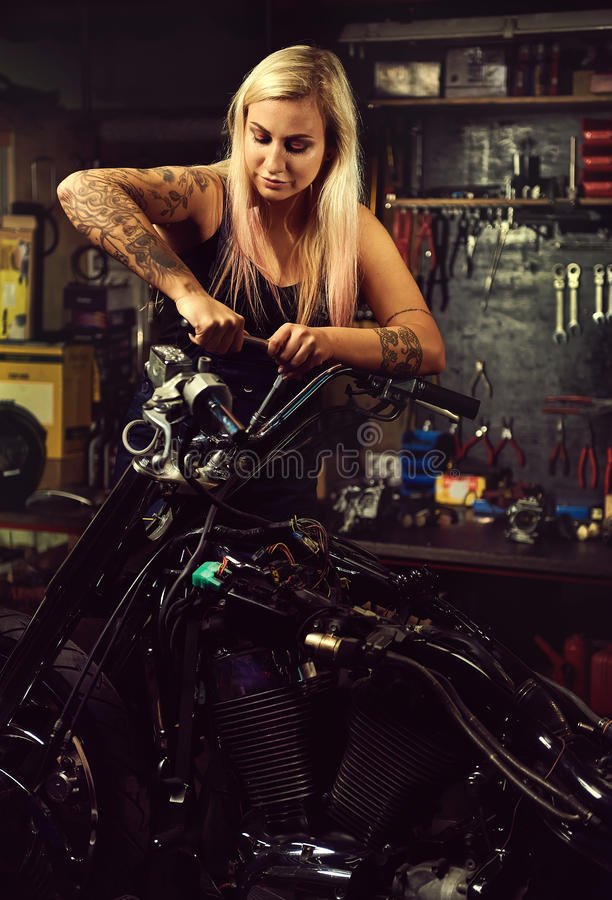 Blond woman mechanic repairing a motorcycle royalty free stock images
