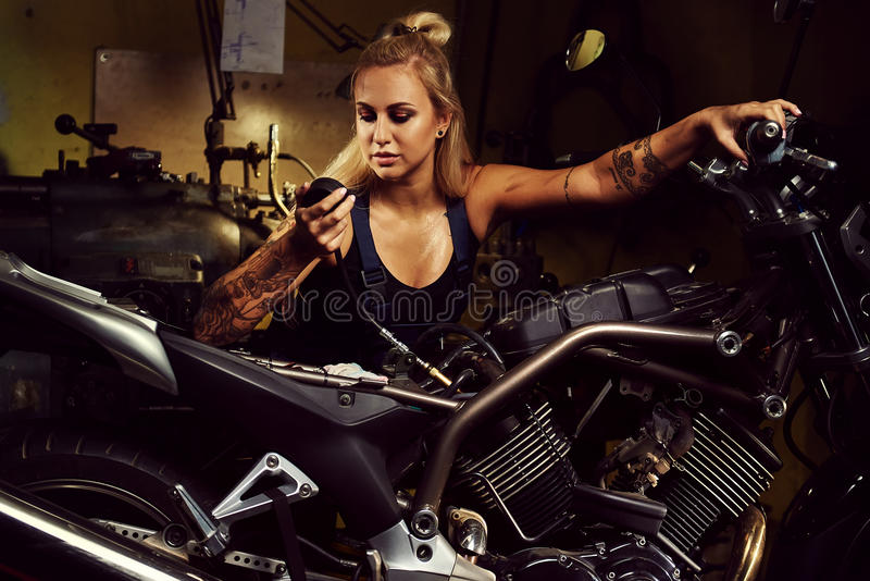 Blond woman mechanic repairing a motorcycle stock images