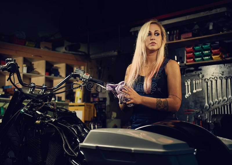 Blond woman mechanic in a workshop royalty free stock image