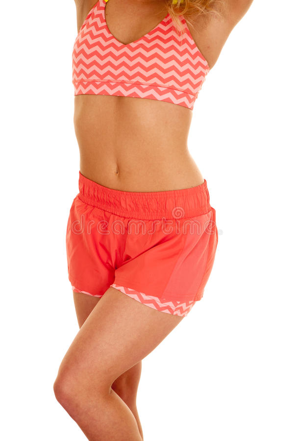 Blond woman orange shorts sports bra body. A woman in her sports bra and shorts ready to work out stock images