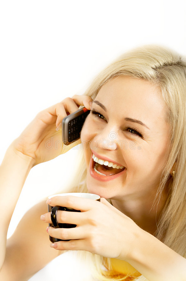 Blond Woman On Phone. Smiling young blond woman holding a phone to her ear and a coffee cup. Isolated on a white background royalty free stock images