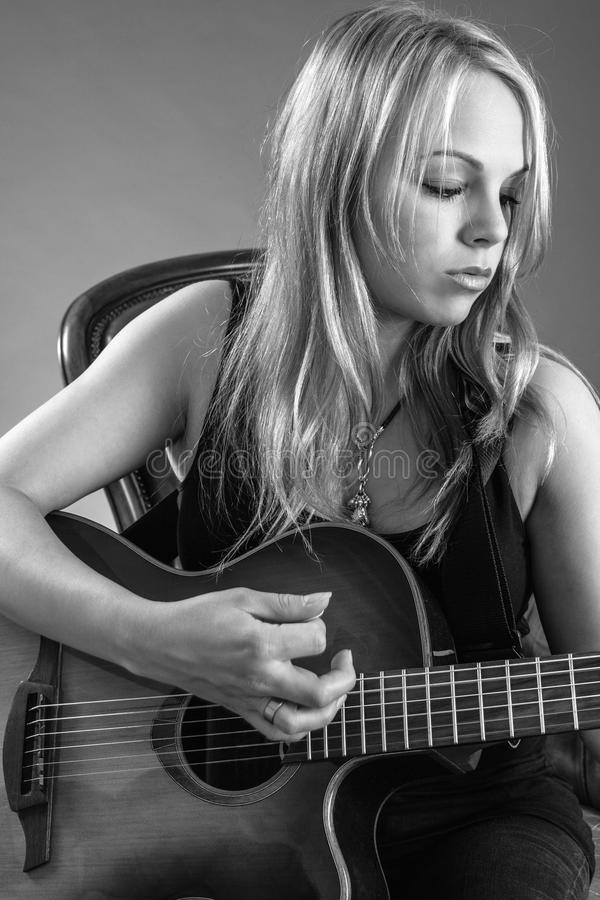 Blond woman playing guitar royalty free stock photography