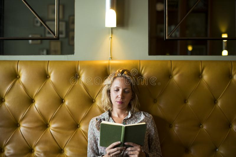 Blond woman reading a book stock image