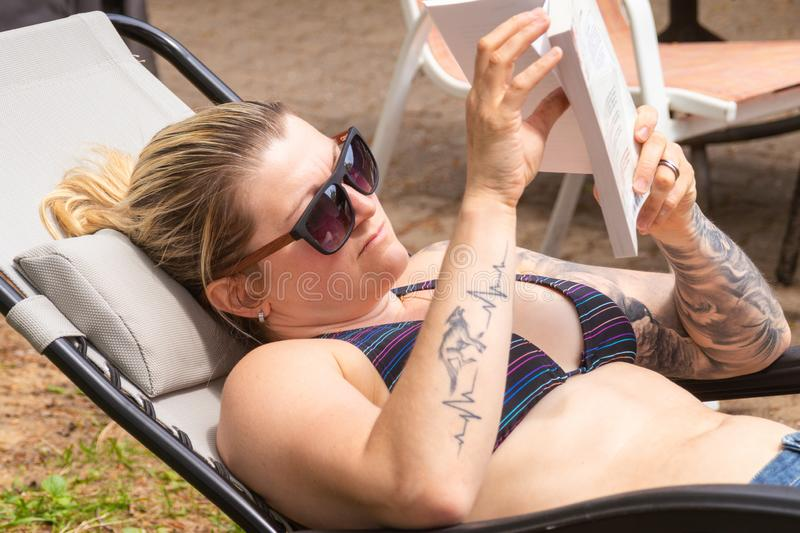 Blond woman reading book by taking sunbath in the house backyard. Blond woman reading a book and taking sunbath in the backyard at summer time royalty free stock photos