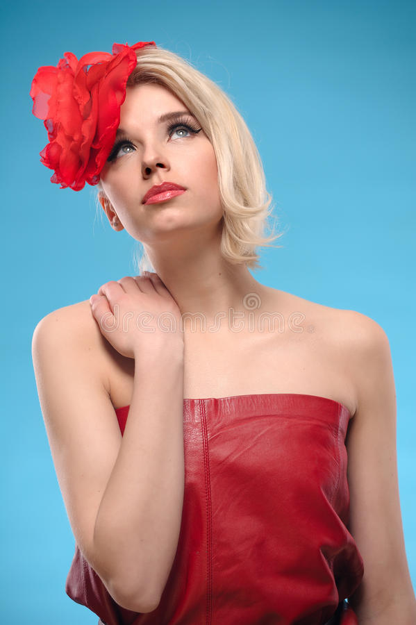 Blond woman with a red flower in hair