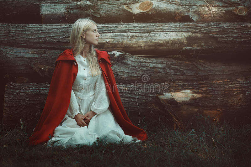 Blond woman with red hooded cloak. Fine art portrait royalty free stock photo