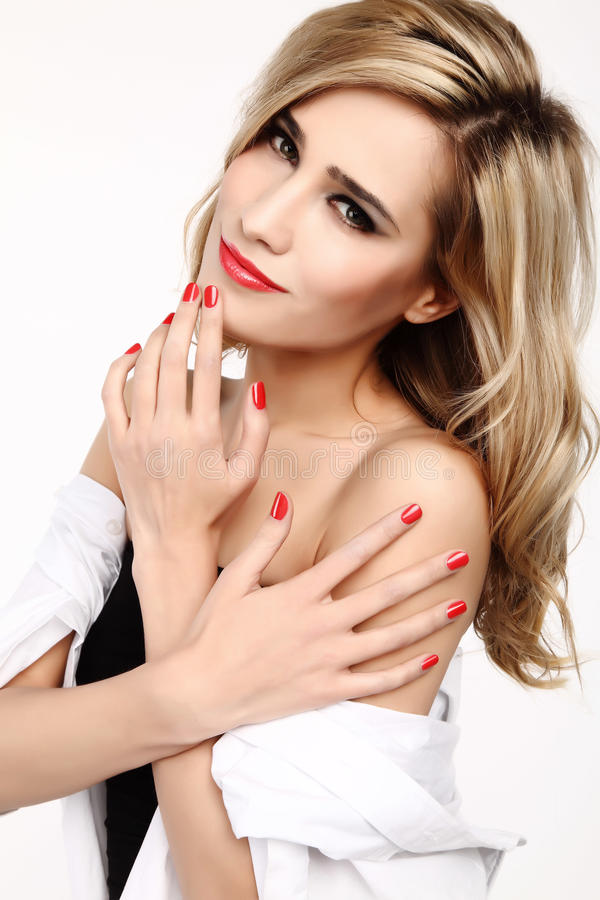 Blond woman with red manicured nails. Beautiful long-haired blonde woman with manicured red nails and red lipstick stock photos