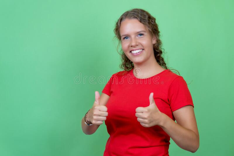 Blond woman with red shirt showing thumb up royalty free stock images