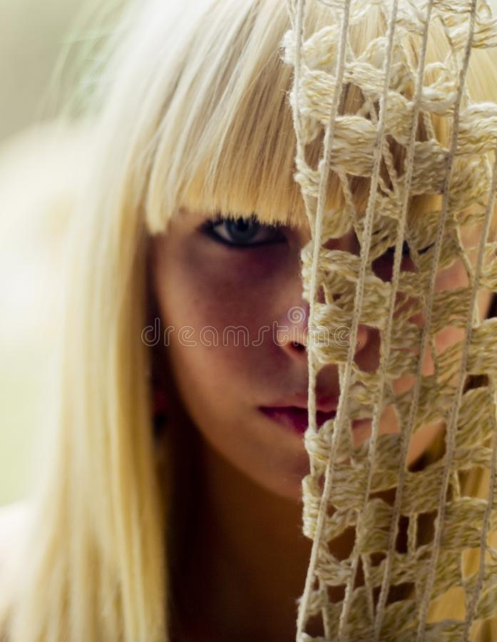 Blond woman's face behind net stock image