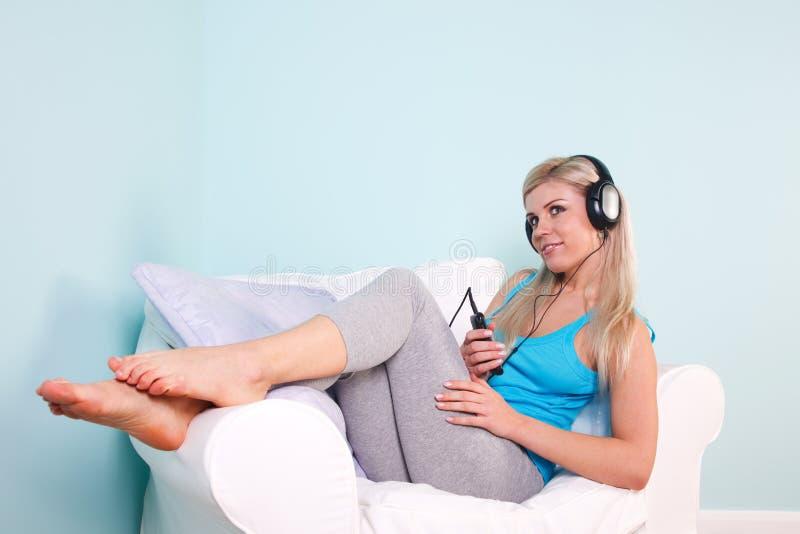 Blond woman sat listening to music stock photo