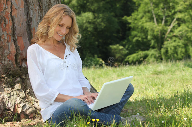 Blond woman sat by tree. With laptop computer stock photos